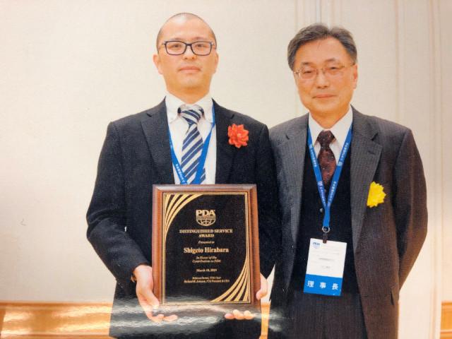 表彰式にて、代理で息子の賀屋拓郎が受領